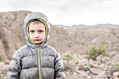 Front view of boy standing in rain shower in Death Valley National Park, California, USA