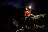 Mforo, Tanzania a village near Moshi, Tanzania. Solar Sister entrepreneur Fatma Mziray checking on her cows in the evening. Before she had the portable solar lantern she and her husband were getting up throughout the night to check on the cows because, de