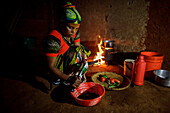 Mforo, Tanzania a village near Moshi, Tanzania. Solar Sister entrepreneur Fatma Mziray cooking dinner on her clean cookstove that uses wood.                                                 Fatma Mziray is a Solar Sister entrepreneur who sells both clean c
