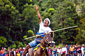 Man raising hand and riding horse with spear at Pasola Festival, Sumba island, Indonesia