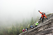 A group of people enjoy a Via Ferrata on a rainy fall day Squamish, British Columbia.