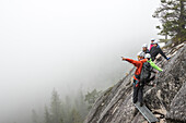 A guide points out into the fog to show something to a group he is guiding on a Via Ferrata in Squamish, British Columbia.