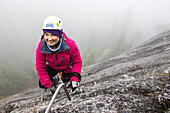 A women reaches for the metal rung while climbing the Via Ferrata in Squamish, British Columbia.