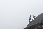 A man and a women slap a hi-five while doing the Via Ferrata on a rainy fall day in Squamish, British Columbia.