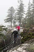A man and a women cross a small suspension bridge that is part of the Via Ferrata in Squamish, British Columbia.