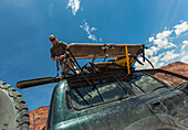 Low Angle View Of Man Unloading Gear From The Top Of Vehicle