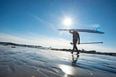 Paddleboarder Heading Into The Cold Atlantic Waters On A Sunny Day