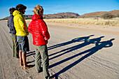 Three men in jackets casting long shadows on dirt road, Erongo region, Namibia