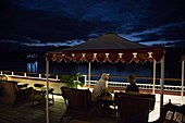 Guests relax under canopy on deck of Ayeyarwady (Irrawaddy) river cruise ship Anawrahta (Heritage Line) at night, near Ngayiphyo, Sagaing, Myanmar
