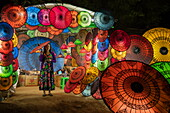 Woman holds umbrella in shop offering colorful umbrellas at night, Nyaung-U, near Bagan, Mandalay, Myanmar