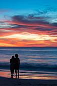 Silhouette of couple embracing at Ngapali Beach at sunset, Ngapali, Thandwe, Myanmar