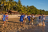 Young men play soccer during official league match on Ngapali beach, Ngapali, Thandwe, Myanmar