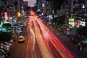 Langzeitbelichtung mit Lichtstreifen von Autos auf der Anawrahta Road in der Abenddämmerung, Yangon, Yangon, Myanmar