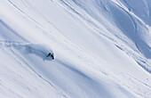 Professioneller Snowboarder und olympischer Goldmedaillengewinner 2014, Jamie Anderson, reitet frisches Pulver an einem sonnigen Tag beim Snowboarding in Haines, Alaska.