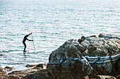 A paddleboarder paddleboarding off the coast of Maine on a cold winter day