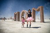 Mother and daughter in front of MOM art at Burning Man