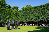 'Frankreich, Paris. 1. Arrondissement. Jardin des Tuileries. Skulptur ''Charaktere III'' von Stephen Martin. Touristen außerhalb eines Restaurants im Hintergrund.'