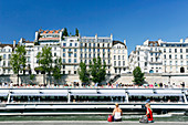 France, Paris. 5th arrondissement. Tourists looking at a passing boat. In the background the Ile Saint Louis.