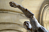 France, Paris, detail of a marble statue of an ancient soldier arm raised at the Louvre Museum