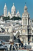 France. Paris 9th district. Bell tower of the Sainte Trinité church and the Sacre-Cœur Basilica