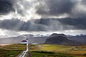 Ingjaldsholskirkja gegen Berge an einem dramatischen stürmischen Tag, in der Nähe von Rif, Snaefellsnes Halbinsel, Island, Polarregionen