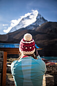 Rear view of woman in knit hat photographing Ama Dablam mountain peak of Himalayas, Dingboche, Khumbu, Nepal