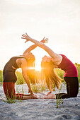 Photograph of two women doing yoga together in Camel Pose (Ustrasana variation), Newport, Rhode Island, USA