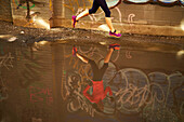 Woman running past puddle in graffiti lined alleyway in Boston, Massachusetts, USA