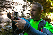 Photograph of man checking camera during canyoneering in Deneau Creek, Hope, British Columbia, Canada