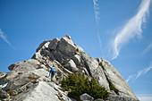 View from below of hiker climbing Needle Peak, Hope, British Columbia, Canada