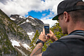 Mountaineer photographing natural scenery with mountains using smartphone, Chilliwack, British Columbia, Canada