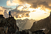 Majestic photograph with mountain climber photographing view at sunset in North Cascade Mountain Range, Chilliwack, British Columbia, Canada