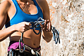 Mid section of female climber holding carabiners, Wyoming, USA