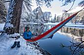 Fotografie des Mannes stillstehend in der Hängematte auf Seeufer während des Winters wandernd, hohe Sierra, Kalifornien, USA.