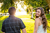 Rear view photograph of couple walking holding hands and woman looking back at camera, Green Lake Park, Seattle, Washington State, USA