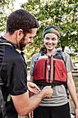 Man adjusting life jacket of female partner outdoors, Portland, Maine, USA