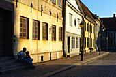 Stortorget in the evening light. Young people are sitting at the doorway, Schweden