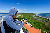 Woman looks from the lighthouse Long Jan, Schweden