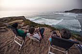 Three young men enjoying the view to the beach Praia da Amoreira,  Aljezur, Faro, Portugal