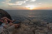 Two young men enjoying the sunset on a cliff at the beach Praia da Amoreira,  Aljezur, Faro, Portugal
