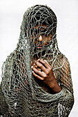 Hispanic boy covered in netting