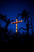 Illuminated crucifix outdoors at night