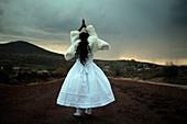 Hispanic girl wearing a white dress outdoors