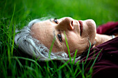 Pensive Caucasian woman laying in grass