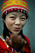 Asian girl wearing traditional hat blowing a kiss