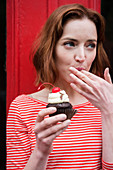 Caucasian woman holding a cupcake licking finger