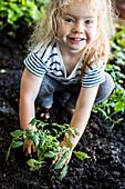Caucasian girl posing with plant in garden