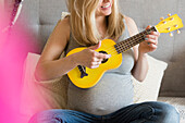 Caucasian and expectant mother playing small yellow guitar