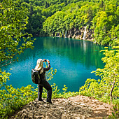 Older Caucasian woman photographing waterfall with cell phone