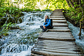 Older Caucasian woman sitting on wooden staircase over waterfalls